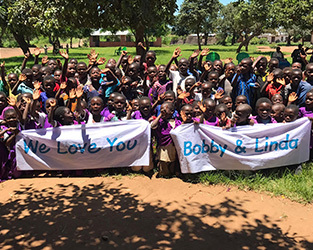 malawi children holding a banner that says 'We love you Bobby and Linda'